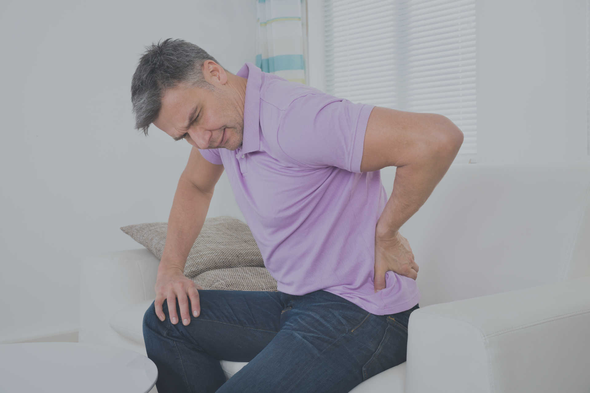 man sitting down holds his lower back in pain